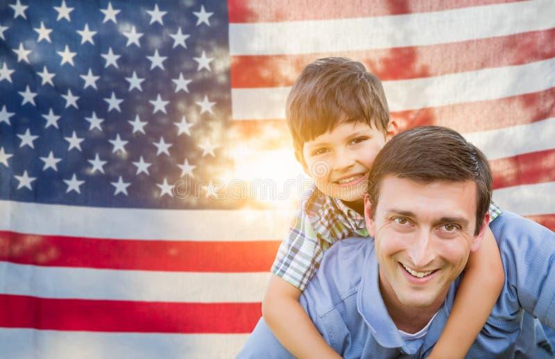 Ojciec z syna Piggyback jazd? Przed flaga ameryka?sk? zdjęcie royalty free
