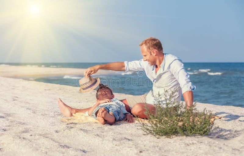 Ojciec z synem wydawał czas wpólnie na dennej piasek plaży w słońcu fotografia stock