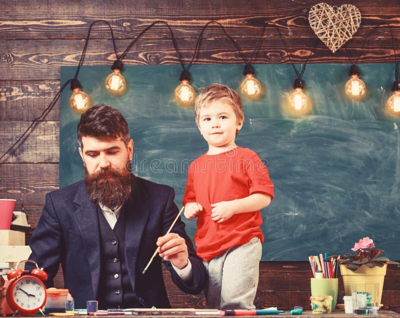 Ojcostwa poj?cie Utalentowany artysta wydaje czas z synem Nauczyciel z brod?, ojciec uczy ma?ego syna remis wewn?trz zdjęcie stock