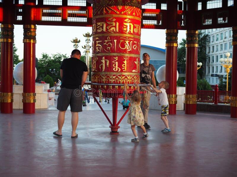 Ojcowie z dziećmi różne narodowości chodzą wokoło czerwonych modlitewnych Buddyjskich bębenów kół Rosja Elista, Czerwiec, - fotografia royalty free