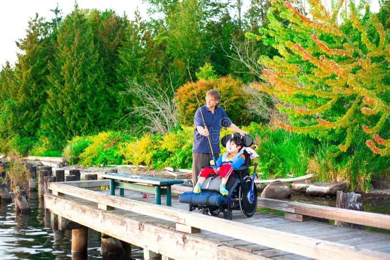 Ojcuje łowić z mola z niepełnosprawnym synem w wózku inwalidzkim zdjęcia stock