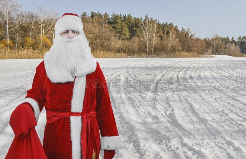 Ojcuje boże narodzenia, Święty Mikołaj jest w drewnach z torbą prezenty zdjęcie stock