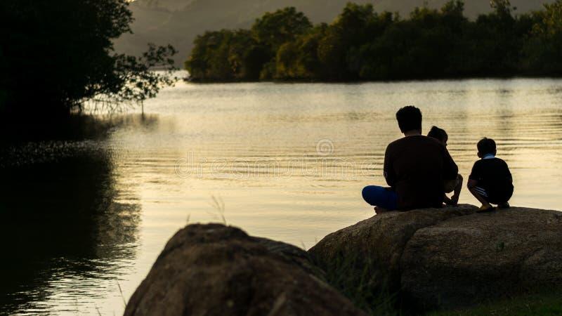 Ojcuje córki Jego syn, siedzi na skałach w parku zdjęcia stock