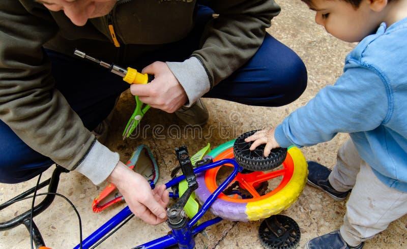 Ojcuje i dwa lat chłopiec załatwia starego kolorowego ośniedziałego rower wpólnie obraz stock
