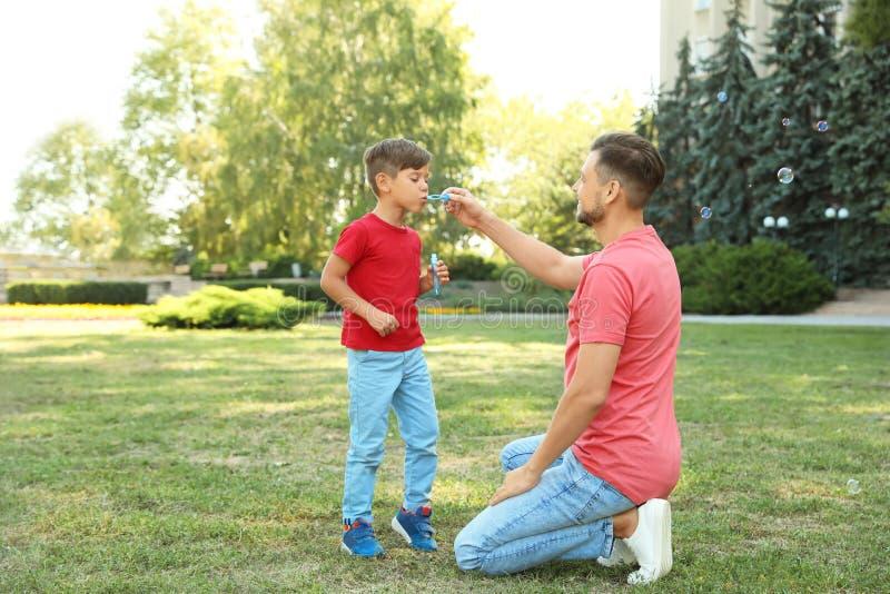 Ojcuje i jego śliczny dziecko bawić się z mydlanymi bąblami obrazy royalty free