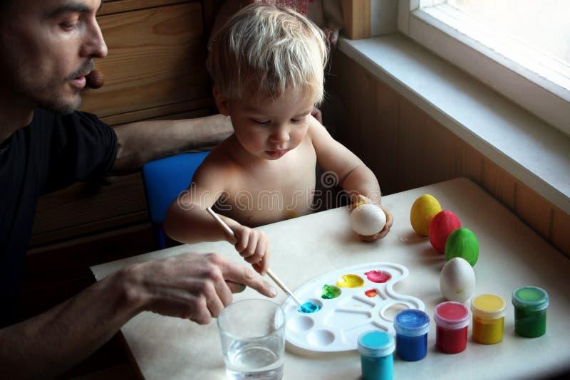 Ojcuje i jego berbecia blond syn farbuje Wielkanocnych jajka wpólnie w domu zdjęcia stock