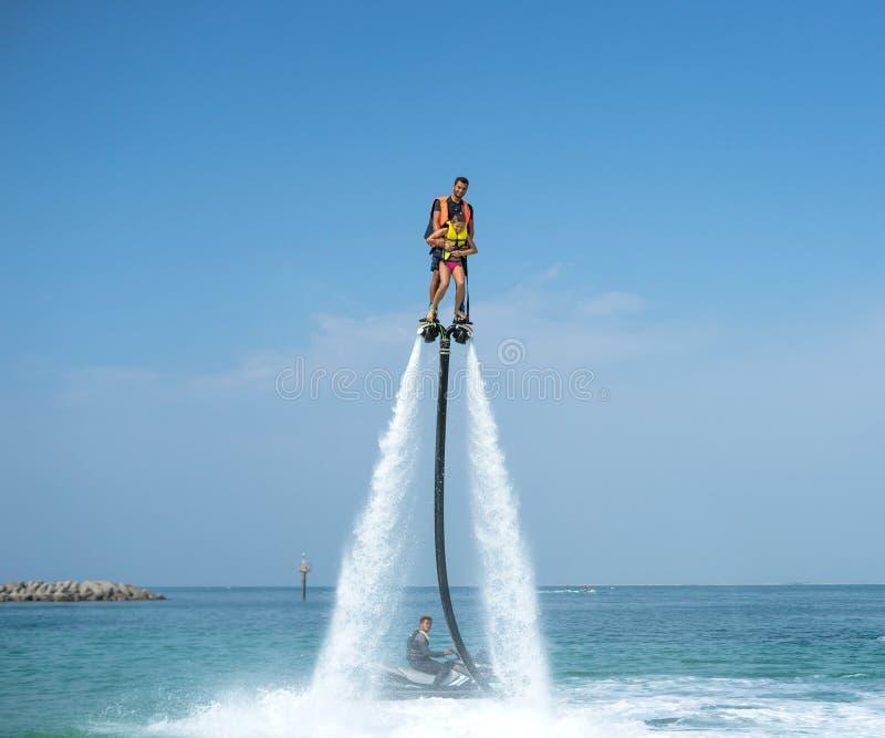 Ojcuje i jego córka pozuje przy nowym flyboard przy tropikalną plażą Pozytywne ludzkie emocje, uczucia, radość Śmieszny śliczny d zdjęcie royalty free