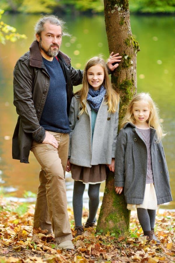 Ojcuje i jego dwa ładnej córki ma zabawę w jesień parku Rodzic i dwa dzieciaka ono cieszy się na ciepłym spadku dniu w mieście zdjęcie stock