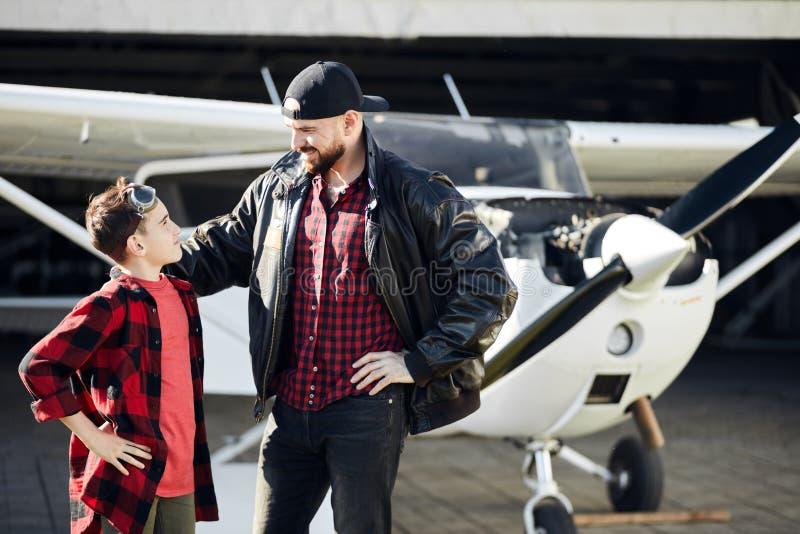 Ojcuje i jego sonstand uśmiechnięty i patrzeje each inny, lekkiego samolotu stojaki za obraz royalty free
