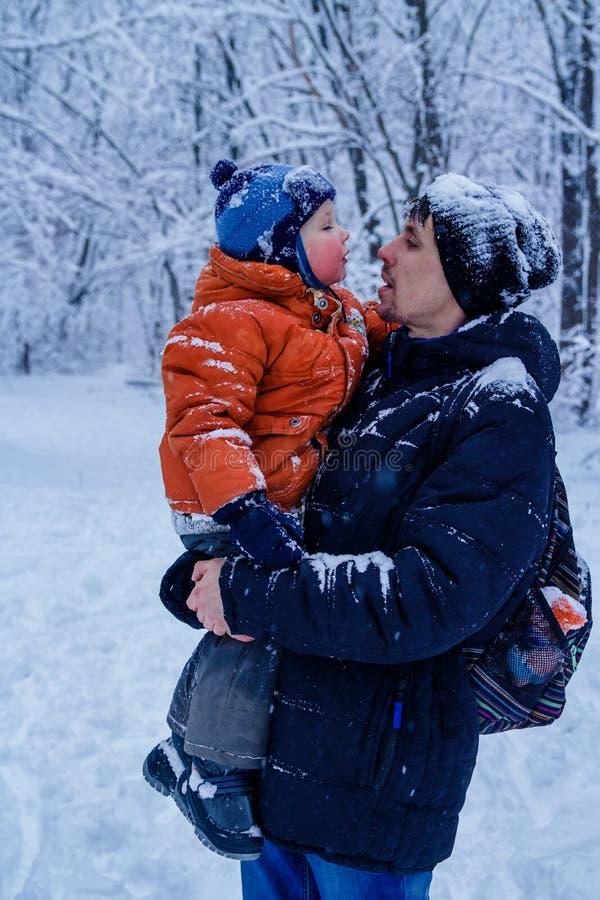 Ojcuje i jego syn bawić się outside, zima las na tle, snowing, szczęśliwy i radosny obrazy stock