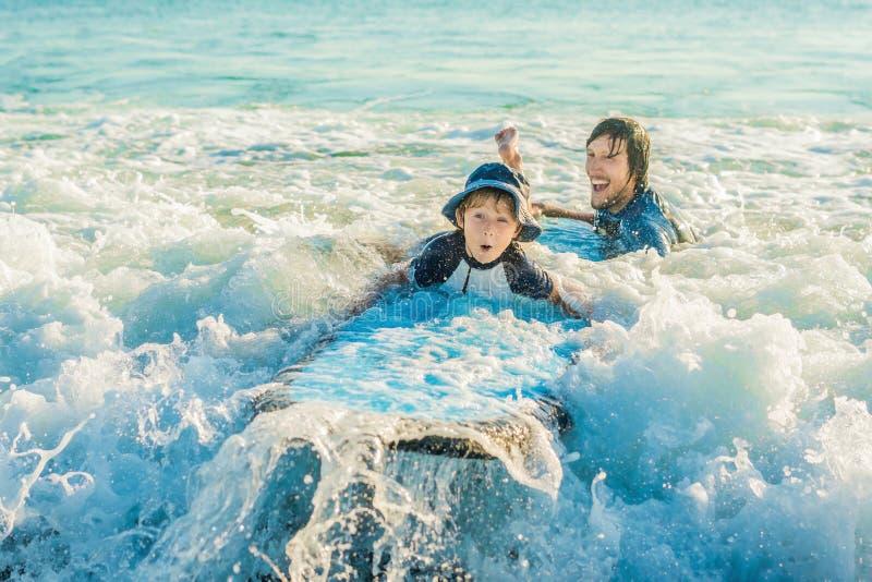 Ojcuje jego młodego syna uczący dlaczego surfować w morzu na wakacje zdjęcie royalty free
