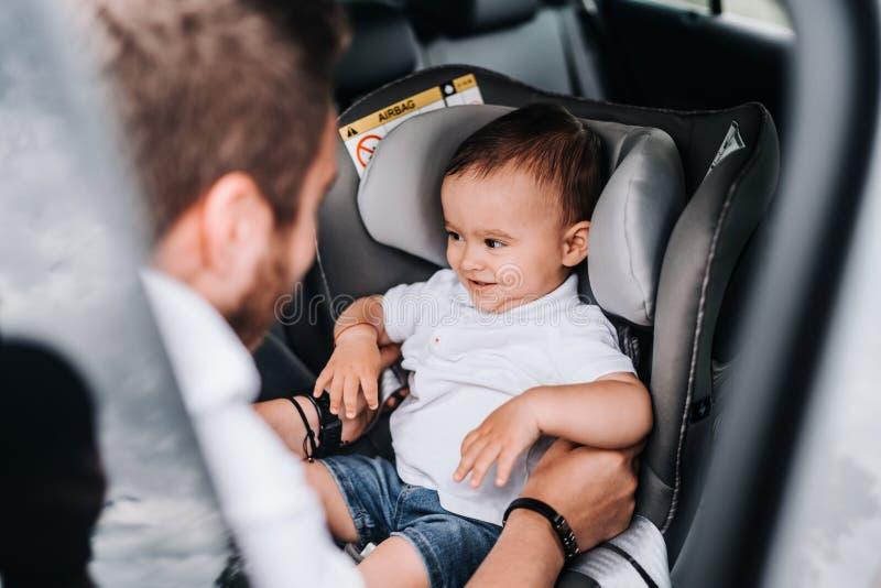 Ojcuje kładzenie jeden roczniaka dziecko w dziecka samochodowym siedzeniu ono uśmiecha się i Stylu ?ycia poj?cie zdjęcia royalty free