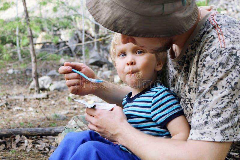 Ojcuje karmić jego syna z łyżką outdoors zdjęcie stock