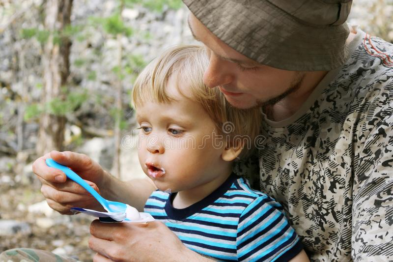 Ojcuje karmić jego syna z łyżką outdoors obrazy royalty free