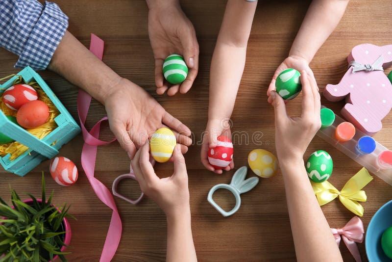 Ojcuje, matka i ich dzieci mienia malujący Wielkanocni jajka na drewnianym tle obraz royalty free