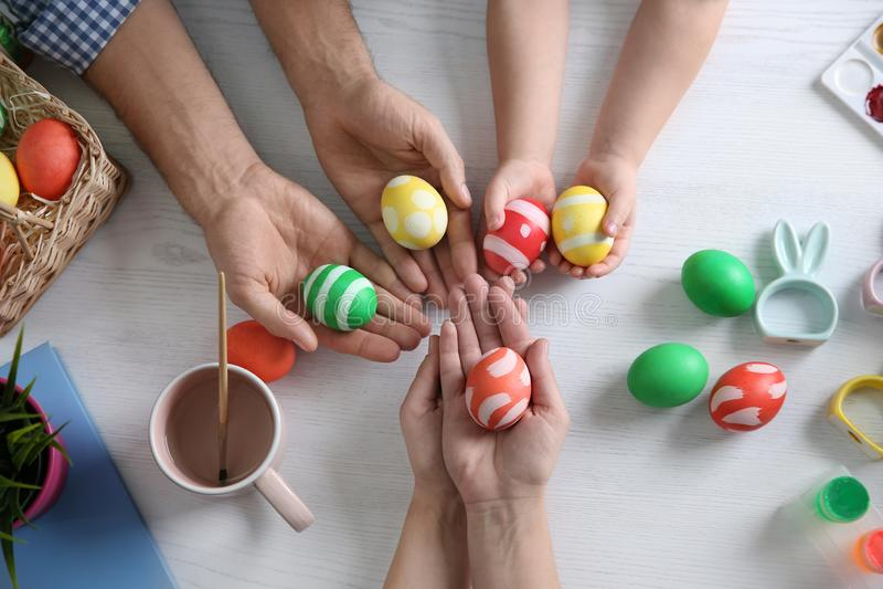 Ojcuje, matka i ich dziecko z malującymi Wielkanocnymi jajkami na drewnianym tle obraz stock