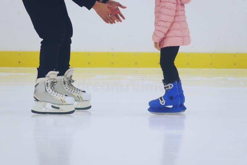 Ojcuje nauczanie córki jeździć na łyżwach przy jazdy na łyżwach lodowiskiem obraz royalty free