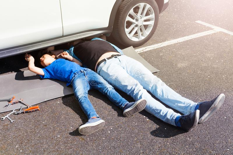 Ojcuje nauczanie syna naprawiać samochodowego lying on the beach pod samochodem zdjęcia royalty free