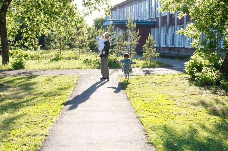 Ojcuje odprowadzenie w parku z dwa córkami przy słonecznym dniem tata z dwa małymi dziećmi mała dziewczynka bieg wokoło obrazy stock