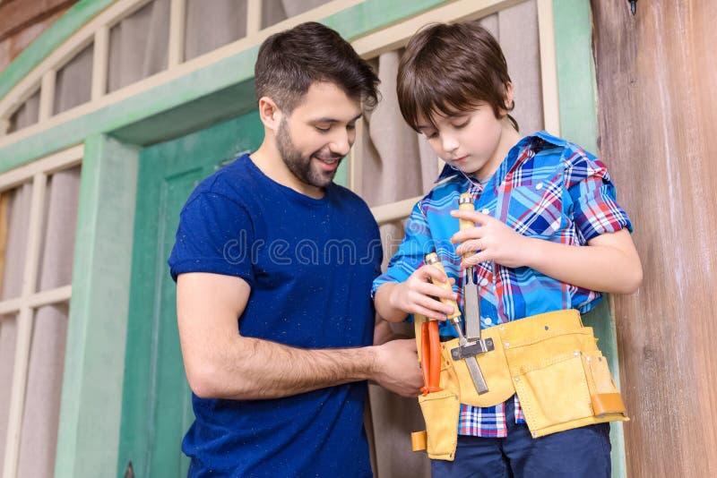 Ojcuje patrzeć syn pozycję w narzędzia mienia i paska narzędziach fotografia royalty free