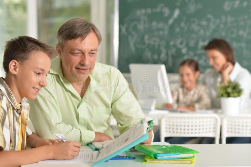 Ojcuje pomagać jego syna robi pracie domowej w sala lekcyjnej obrazy stock