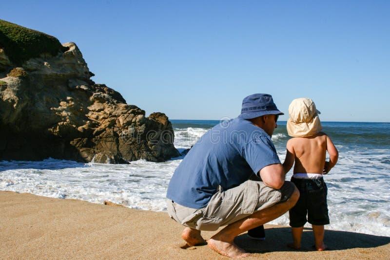 Ojcuje przy plażą od b i 2 roczniaka syna oceanu okładzinowej fala zdjęcia royalty free