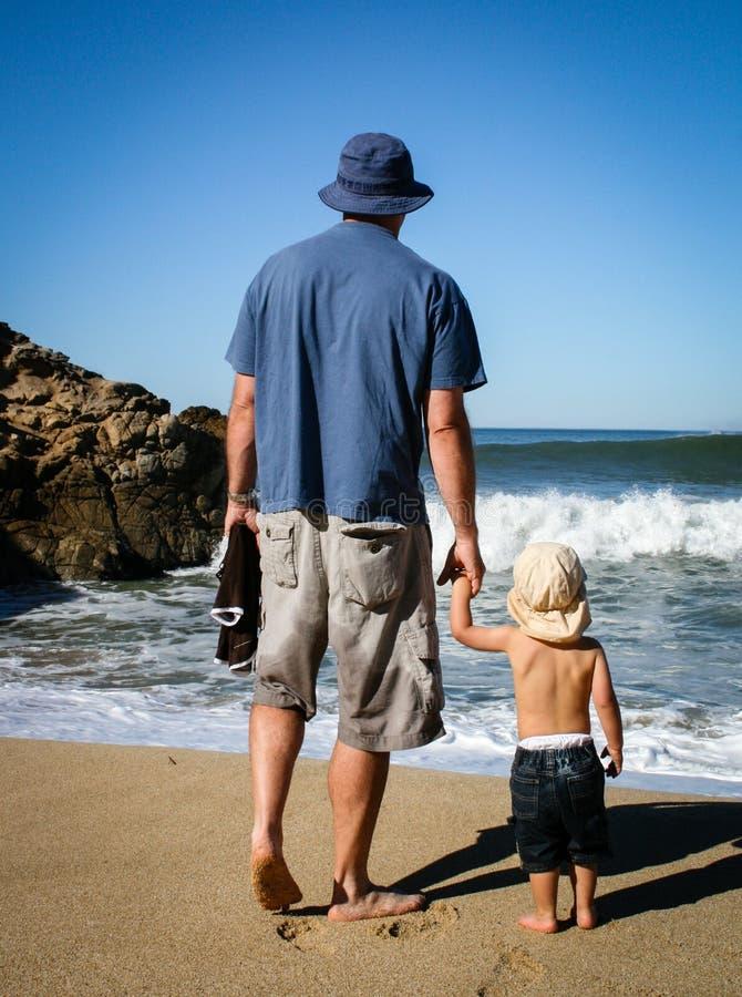 Ojcuje przy plażą od b i 2 roczniaka syna oceanu okładzinowej fala obraz royalty free