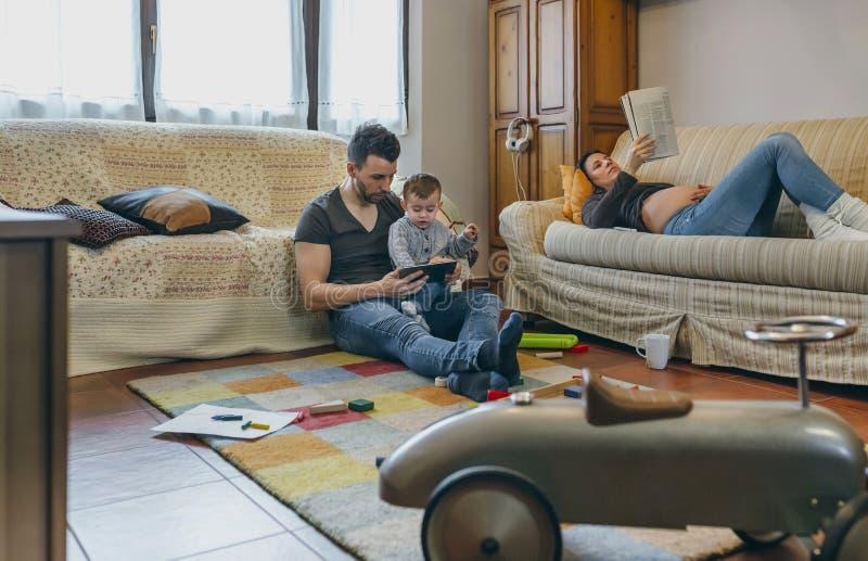 Ojcuje przyglądającą pastylkę z małym synem podczas gdy ciężarna matka czyta magazyn fotografia stock