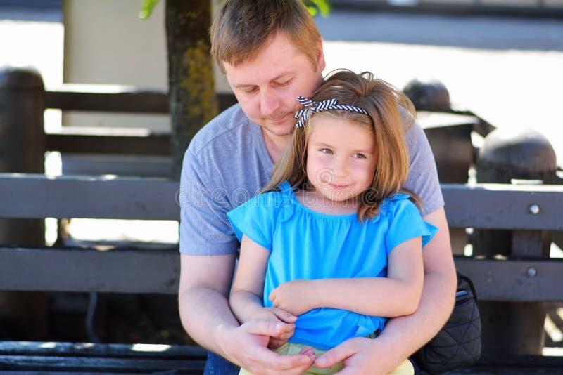 Ojcuje przytulenie córki na ławce w parku na pogodnym letnim dniu obraz royalty free