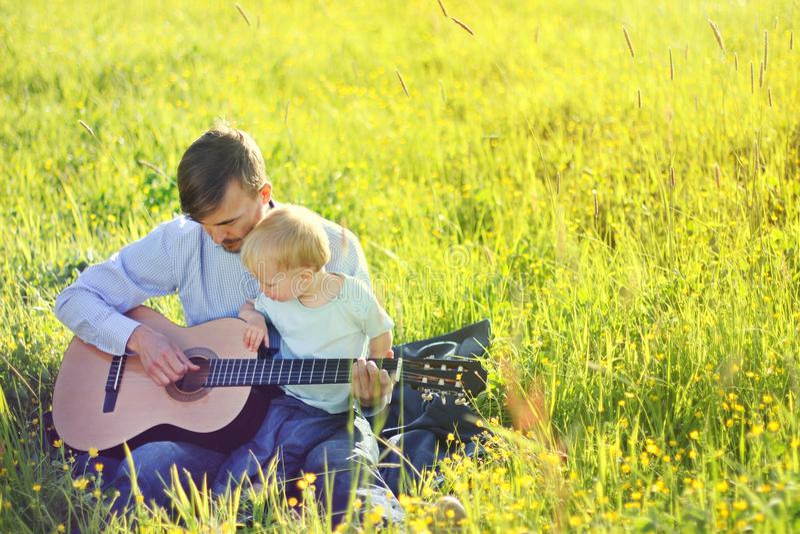 Ojcuje uczyć jego syna bawić się gitarę plenerową Czasu wpólnie syn i tata kosmos kopii zdjęcia stock