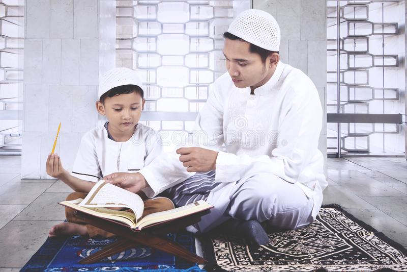 Ojcuje uczyć jego syna czytać koran fotografia royalty free