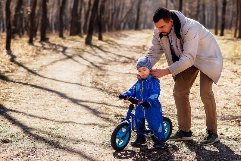 Ojcuje ustawiać nakrętkę jego berbecia syn w błękitnym kombinezonie w parku Dziecko siedzi na błękitnym balansowym rowerze fotografia stock