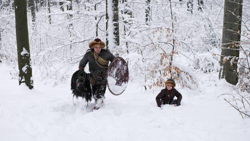Ojcuje Viking z jego synem iść w zima lesie obraz stock