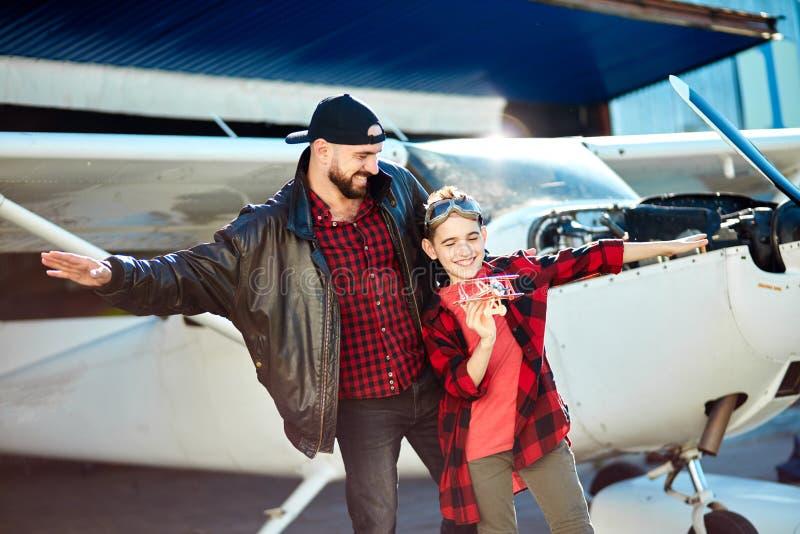 Ojcuje wraz z rękami jak samolotowi skrzydła oddzielnie i jego syn pozycja obraz stock