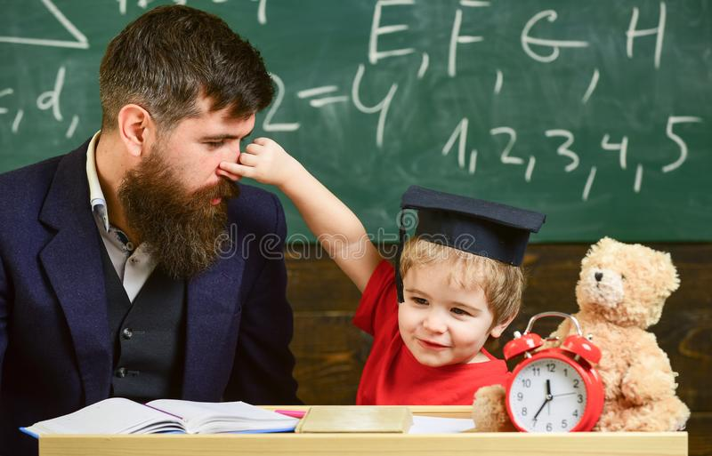 Ojcuje z brodą, nauczyciel uczy syna, chłopiec, podczas gdy dziecko szczypa jego nos Dzieciak rozochocona sztuka z tata figlarnie zdjęcia royalty free