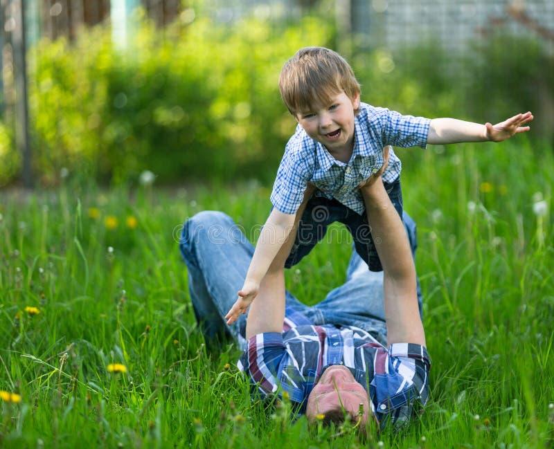 Ojcuje z jego małym synem bawić się w trawie na lecie zdjęcie royalty free