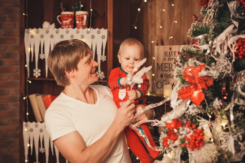 Ojcuje z jego Małym synem dekoruje choinki z zabawkami a obraz stock