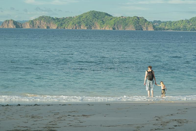 Ojcuje z plecakiem trzyma rękę jego syn morzem Wchodzić do wodę przeciw tłu piękne wyspy zdjęcia stock
