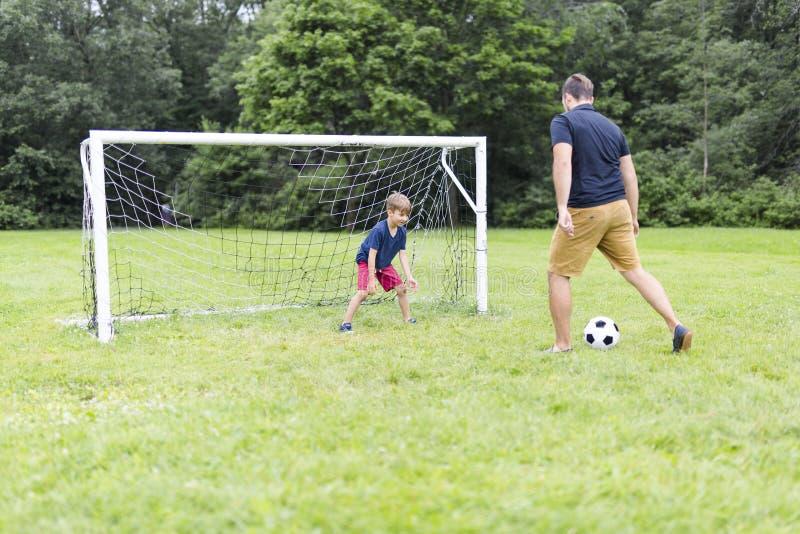 Ojcuje z synem bawić się futbol na futbolowej smole fotografia royalty free