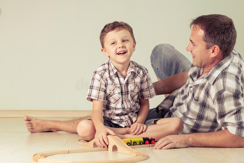 Ojczulek z chłopiec bawić się z zabawka pociągiem na podłoga przy zdjęcia royalty free