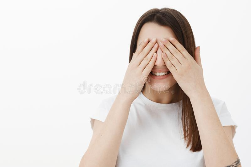 Ojeada de la promesa no Retrato de la sorpresa anticiapting de la muchacha emocionada y feliz del b-día con los ojos y las palmas imagenes de archivo