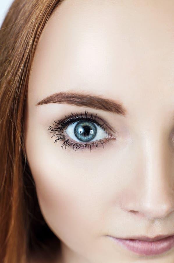 Ojo azul del primer de la mujer joven del pelirrojo foto de archivo