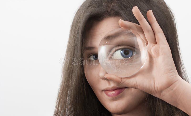 Ojo azul femenino que mira a través de la lupa fotos de archivo