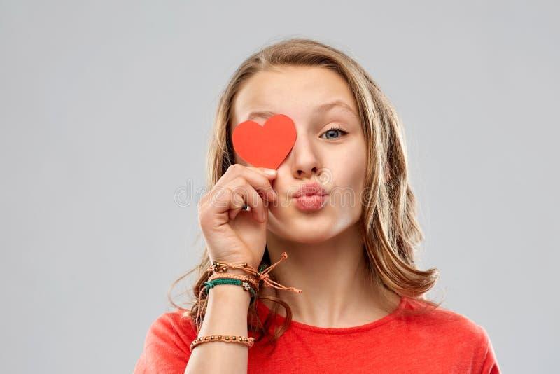 Ojo de la cubierta del adolescente con el corazón rojo imagen de archivo