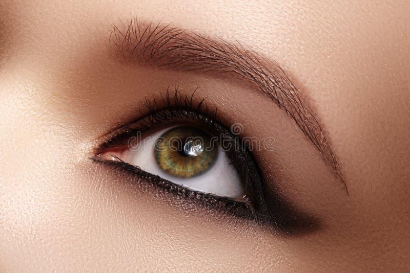 Ojo femenino con maquillaje oscuro, grandes frentes del primer de las formas r Lápiz de ojos de la moda, lápiz foto de archivo libre de regalías