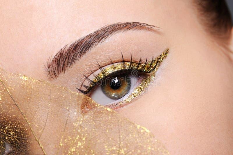 Ojo femenino con un maquillaje de oro de la flecha foto de archivo libre de regalías