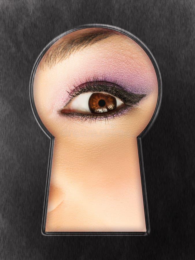 Ojo femenino curioso en un ojo de la cerradura imagenes de archivo