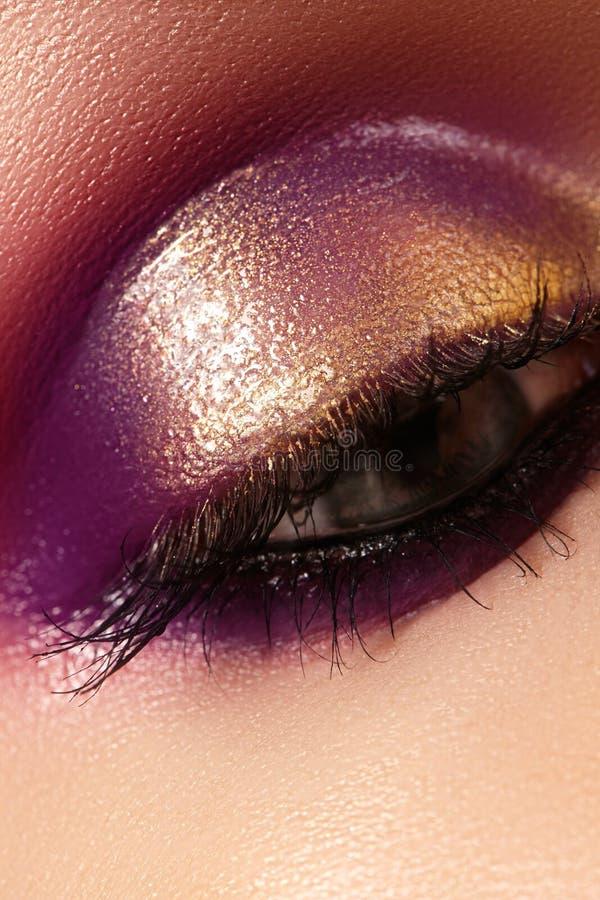 Ojo femenino del primer con maquillaje brillante de la moda hermosa El oro brillante hermoso, sombreador de ojos púrpura, mojó br fotos de archivo