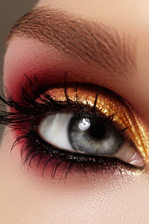 Ojo femenino del primer con maquillaje brillante de la moda Oro hermoso, sombreador de ojos rojo, brillo, lápiz de ojos negro Cej imagenes de archivo
