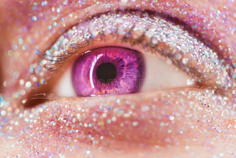 Ojo femenino violeta o rosado macro con el sombreador de ojos del brillo, chispas coloridas, cristales Fondo de la belleza, encan foto de archivo libre de regalías